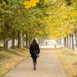 A woman walking over a pedestrian path across the trees fallen leaves