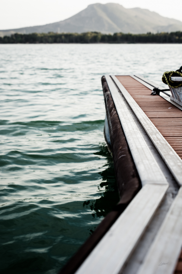 Detail focused on a part of a jetty in a lake with no boats in it
